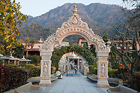 India, Rishikesh.  Courtyard of the Parmarth Niketan Ashram.  A blue-tinted statue of Shiva is under the second arch.