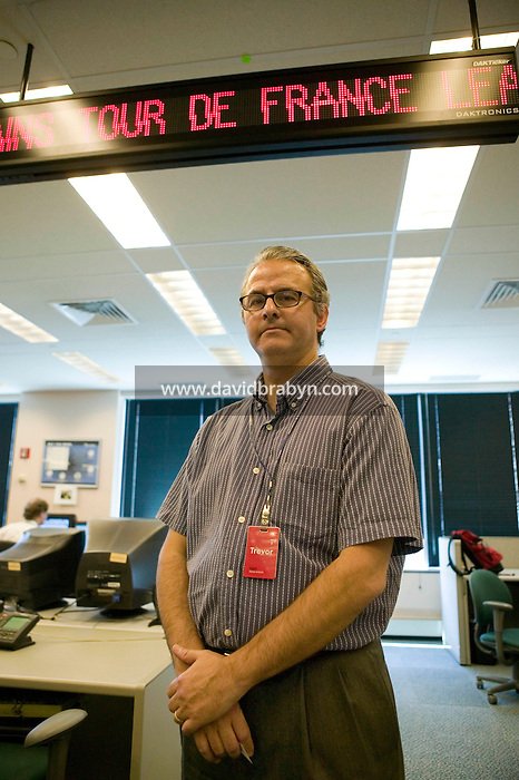 21 July 2005 - Jersey City, NJ - Hammad Jawdat, editor of Dow Jones' famous Times Square zipper, poses under the backup zipper in the Dow Jones Newswire offices in New Jersey, USA, which displays a live version of the Times Square zipper for control purposes, 21 July 2005.