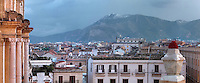 Columns of the Baroque facade of the chiesa di San Domenico (Church and Oratory of San Domenico), 1458 - 1480, on the left, city rooftops view and snow-capped mountains in the distance, Palermo, Sicily, Italy. Picture by Manuel Cohen