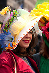 Woman wearing a red trenchcoat and a large hat decorated with flowers and birds in the Easter Parade on Fifth Avenue in New York City