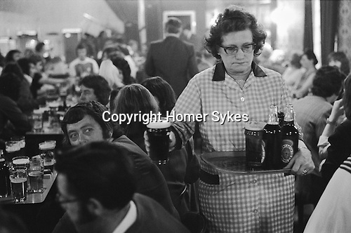 Byker, Newcastle upon Tyne. 1973<br /> Saturday night at Byker &amp; St. Peters Working Men's Social Club, bar staff serve up pints and bottles of Newcastle Brown Ale.