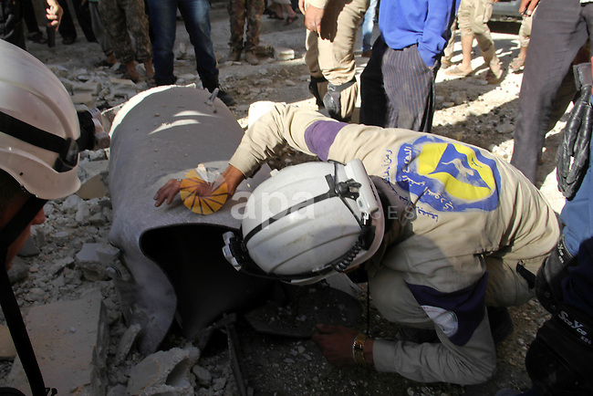 A member of Syrian civil defense inspects unexploded barrel bomb, thrown by Syrian government forces in Bab al-Nairab district in the northern Syrian city of Aleppo, June 30, 2015. Photo by Ameer al-Halbi