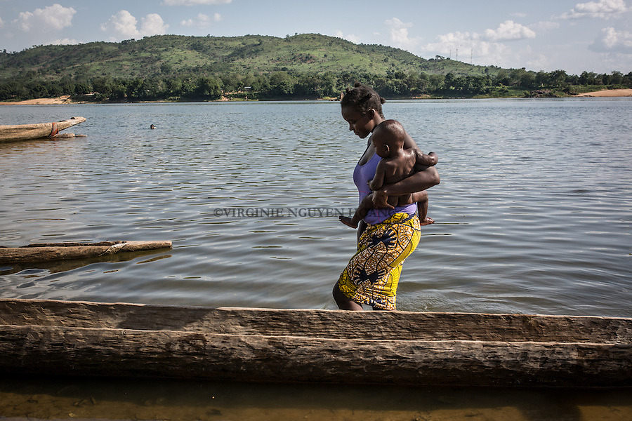 CAR, Bangui:  A woman walk into the Oubangui reiver after cleaning her baby. The river is often used by people of Bangui to clean themselves and to do their laundry. 20th April 2016<br /> <br /> RCA, Bangui : Une femme marche dans la rivi&egrave;re Oubangui apr&egrave;s avoir lav&eacute; son b&eacute;b&eacute; . La rivi&egrave;re est souvent utilis&eacute;e par des personnes de Bangui pour se laver et faire leur lessive . 20 Avril 2016