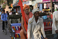 Rickshaw wallah or puller with Sadhu or holy man in back. Varanasi, Uttar Pradesh, India