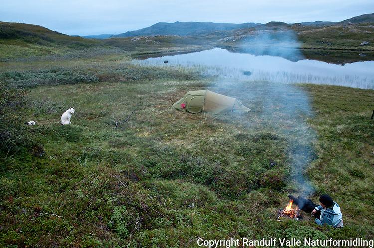 Jente fyrer bål i leiren ved lite vann på Sørøya. ---- Woman by camp fire.