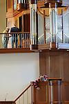 Foto: VidiPhoto<br /> <br /> OPHEUSDEN - Terwijl het vernieuwde en imposante pijporgel met 2600 pijpen wordt gestemd, verrichten vrijwilligers maandag de laatste werkzaamheden in de gloednieuwe megakerk  van de Gereformeerde Gemeente in Opheusden. De kerkzaal -verdeeld over twee bouwlagen- biedt plek aan 1750 kerkgangers en is uit te breiden tot 1900 zitplaatsen. De enorme ruimte heeft een vloeroppervlakte van bijna 3500 vierkante meter. Verder zijn er zes grote vergaderzalen en enkele kleinere vergaderplekken. Woensdag wordt de kerk officieel in gebruik genomen met een kerkdienst, geleid door de plaatselijke predikant ds. G. M. de Leeuw. De kerkelijk orthodox-christelijke  gemeente groeit al jaren sterk, waardoor het vorige -en al uitgebreide- kerkgebouw met 1500 zitplaatsen gesloopt moest worden. Het nieuwe godshuis behoort tot &eacute;&eacute;n van de grootste reformatorische kerken van Nederland. De bouwkosten bedragen 6,7 miljoen euro. Foto: Vrijwilliger de 14-jarige Rik Tijssen uit Opheusden verwijdert het stof van banken, doopvont en kansel.