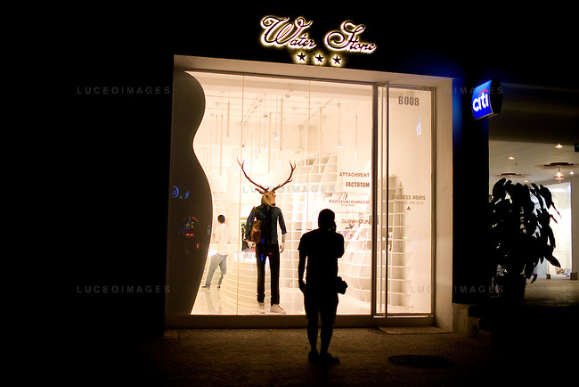 A tourist stares in at store window mannequin in downtown Beijing, China on Saturday, August 9, 2008.  Kevin German