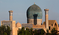 General view of Gur-Emir Mausoleum with the cupula of the Ak-Sarai Mausoleum, (White Palace) in the distance (left), Samarkand, Uzbekistan, pictured on July 18, 2010, in the afternoon. Gur-Emir Mausoleum, or Tomb of the Ruler, was built by Timur in 1404 for his favourite grandson, Mohammed Sultan, and became the mausoleum for the Timurid dynasty. The simply formed building is an octagonal drum beneath an azure fluted dome (diameter: 15m, height: 12.5m). Its walls are tiled in blue and white geometric and epigraphic patterns including the words 'God is Immortal' in 3m. high white Kufic script around the top of the drum. The Ak-Sarai Mausoleum, located South East of the Gur-Emir Mausoleum, is also a Timurid tomb, commissioned by Abu Sa'id (1451-1468/9). Samarkand, a city on the Silk Road, founded as Afrosiab in the 7th century BC, is a meeting point for the world's cultures. Its most important development was in the Timurid period, 14th to 15th centuries. Picture by Manuel Cohen.