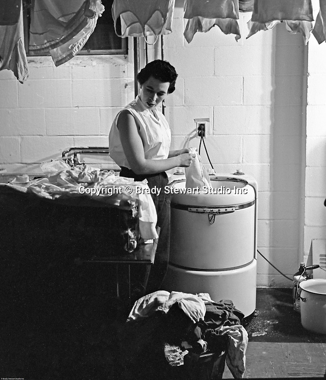 Bethel Park PA:  Marjorie Stewart is the model washing clothes in the new Kenmore washing machine.  The photograph was used in an advertisement for Sears - 1953.