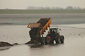 HARLINGEN, 14 maart 2011.  Bij het schoonmaken van het Harlinger strand naast de Zuiderpier raakte een landbouwtractor met kiepaanhanger van Loonbedrijf Tolsma uit Tzum vast in het zand en slib. Een graafmachine van hetzelfde loonbedrijf probeerde de trekker los te trekken, maar kwam eveneens vast te zitten. Ondertussen werd het vloed en kwamen beide grondverzetmachines in het zeewater te staan. Een graafmachine op rupsbanden werd ingezet, maar kon evenmin de tractor met kipper en graafmachine loskrijgen. Bij de reddingsactief bij opkomend water verloor de graafmachine één van de rupsbanden, maar kon zichzelf nog net in veiligheid stellen. Een ponton met kraan werd vanuit de haven van Haringen ingezet, maar kon door de ondiepte niet dicht genoeg bij de tractor en graafmachine komen. In de loop van de avond en nacht wordt opnieuw getracht de beide machines te bevrijden..De tractor met kipper was vastgeraakt in het zand toen het bij laag water over het drooggevallen strand langs de Zuiderpier richting havenmond reed om daar langs de laagwaterlijn slib te storten. Bij opkomend tij zou het zeewater het slib mee terug de Waddenzee nemen. Het slib was verzameld op het hoger gelegen strand, nabij de Waddenzeedijk.