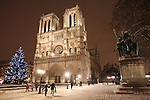 Paris, France , and continental Europe is gripped by heavy snow and arctic conditions in the run up to Christmas December 2010. Transport is just about brought to a standstill, with airports and train stations closed down or running slow. On the other hand Paris is rarely snowbound and as such  is idyllic and remains an attraction to tourists and local Parisiens alike.//Notre Dame Cathedral in the snow at night with a Christmas tree