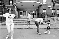 "USA. New York City. Spanish Harlem. Nina (L) wears a self-designed t-shirt with the written words "" I love men, money, sex "". She also dances on the sidewalk. Sala (C), her daughter, stands on the staircase. Bente (CR), her niece, plays with Papo (R). The Puerto Rican family lives below the poverty line and receives public assistance (AFDC, Home Relief, Supplemental Security Income and Medicaid). The family resides in units managed by the New York City Housing Authority (NYCHA) which provides housing for low income residents. NYCHA administers rental apartments in facilities, popularly known as ""projects"". Spanish Harlem, also known as El Barrio and East Harlem, is a low income neighborhood in Harlem area. Spanish Harlem is one of the largest predominantly Latino communities in New York City. 26.06.88 © 1988 Didier Ruef .."