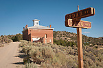Historic abandoned brick Nye Co. Courthouse behind street sign: Cedar St. and Dago Way