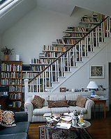 Books line the walls of the staircase in this open-plan living room