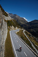 A touring cyclist climbs a high pass in the Swiss Alps - Switzerland