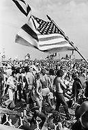 Watkins Glen, NY. July 28th, 1973. <br /> Crowd under flaming flag.<br /> The Summer Jam at Watkins Glen was a 1973 rock festival which once received the Guinness Book of World Records entry for &quot;Largest audience at a pop festival.&quot; An estimated 600,000 rock fans came to the Watkins Glen Grand Prix Raceway outside of Watkins Glen, New York on July 28, 1973, to see The Allman Brothers Band, Grateful Dead and The Band perform.<br /> Similar to the 1969 Woodstock Festival, an enormous traffic jam created chaos for those who attempted to make it to the concert site. Long and narrow country roads forced fans to abandon their vehicles and walk 5&ndash;8 miles on that hot summer day. 150,000 tickets were sold for $10 each, but for all the other people it was a free concert. The crowd was so huge that a large part of the audience was not able to see the stage; however, twelve huge sound amplifiers, installed courtesy of legendary promoter Bill Graham, allowed the audience to at least hear.
