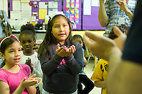 "A pupil cups her hands to express ""my school"" as the teacher says ""my school"" in Arabic. First and second graders learn Arabic at P.S. 368-Hamilton Heights School in Harlem in New York on Wednesday, May 23, 2012. The program is the first at the K-5 school level in New York City Public Schools.  © Frances M. Roberts)"