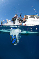 Diver doing a giant stride entry from Makena Mele boat Molokini Maui Hawaii.