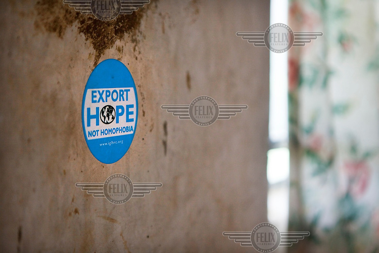 A sticker on the wall of murdered gay rights activist David Katos' house. It reads 'Export Hope Not Homophobia'. He was murdered soon after the tabloid newspaper Rolling Stone published his name on its front page. The paper infamously ran a homophobic story with the headline 'Hang Them'