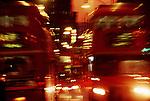 Doubledecker buses carry passengers through London at dusk