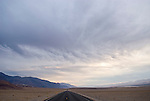 A gathering storm above the highway rolling over the desert hills near Badwater, Death Valley National Park, Calif.