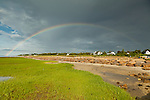 A full rainbow arches over Paine's Creek Beach in Brewster.