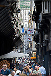 Shoppers walk the narrow street in the Spaccanapoli shopping district in Naples.