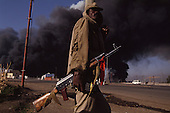 Addis Ababa, Ethiopia<br /> June 4,1991<br /> <br /> An Ethiopian People's Revolutionary Democratic Front (EPRDF), fighter patrols an exploding ammunition depot set alight by former government supporters.<br /> <br /> In late May 1991 the long civil war in Ethiopia came to a climax when the alliance of four rebel groups, the EPRDF, toppled the authoritarian government of Mengistu Haile-Mariam and took control of Addis Ababa and the nation. The governing regime declared a cease-fire and fled. <br /> <br /> In July 1991 the 24 different groups met in the capital and established a multi-party provisional government headed by Meles Zenawi, the Tigray Rebel Leader, to lead the country to its first free elections within two years.