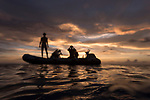 Kauehi Atoll, Tuamotu Archipelago, French Polynesia; scuba divers on an inflatable boat are silhouette against a sunset sky after a dive