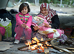 Six-year old Miriam, a refugee from Afghanistan, warms herself by a fire as she sits beside her mother and a younger sibling inside a refugee processing center in the Serbian village of Presevo, not far from the Macedonian border. Hundreds of thousands of refugees and migrants--including many children--have flowed through Serbia in 2015, on their way from Syria, Iraq and other countries to western Europe.