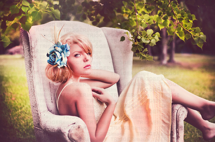 Close up of young woman with blonde hair sitting in a comfy old lounge chair in a garden