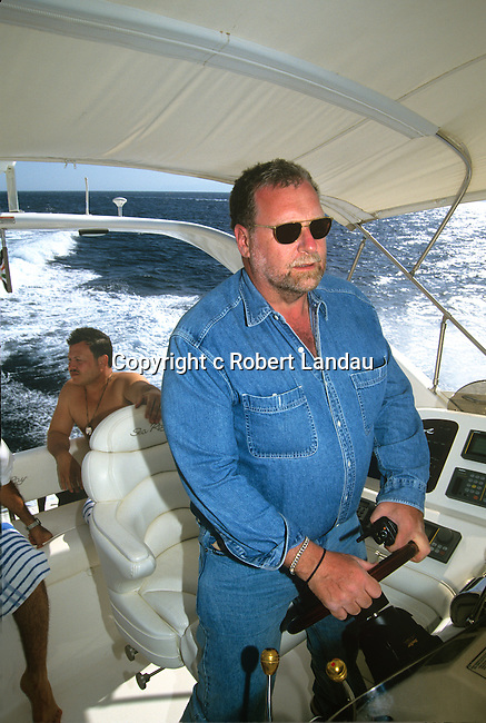 Peter Greenberg piloting King Abdulah's private yach with King Abdullah II of Jordan in background, Aqaba, Jordan