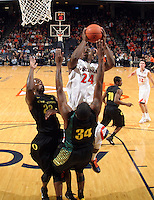 Dec. 17, 2010; Charlottesville, VA, USA; Virginia Cavaliers guard K.T. Harrell (24) shoots over Oregon Ducks guard Teondre Williams (22) and Oregon Ducks forward Joevan Catron (34) during the first half of the game at the John Paul Jones Arena. Mandatory Credit: Andrew Shurtleff-
