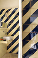 On the walls of the bathroom cream and black ceramic tiles have been arranged in a striking diagonal design