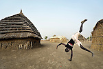 Displaced by war, a boy does a handstand in Agok, a town in the contested Abyei region where tens of thousands of people fled in 2011 after an attack by soldiers and militias from the northern Republic of Sudan on most parts of Abyei. Although the 2005 Comprehensive Peace Agreement called for residents of Abyei--which sits on the border between Sudan and South Sudan--to hold a referendum on whether they wanted to align with the north or the newly independent South Sudan, the government in Khartoum and northern-backed Misseriya nomads, excluded from voting as they only live part of the year in Abyei, blocked the vote and attacked the majority Dinka Ngok population. The African Union has proposed a new peace plan, including a referendum to be held in October 2013, but it has been rejected by the Misseriya and Khartoum. The Catholic parish of Abyei, with support from Caritas South Sudan and other international church partners, has maintained its pastoral presence among the displaced and assisted them with food, shelter, and other relief supplies.
