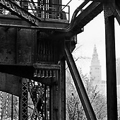 The Terminal Tower seen through the steel beams of a railroad bridge over the Cuyahoga River in the flats. Cleveland Ohio