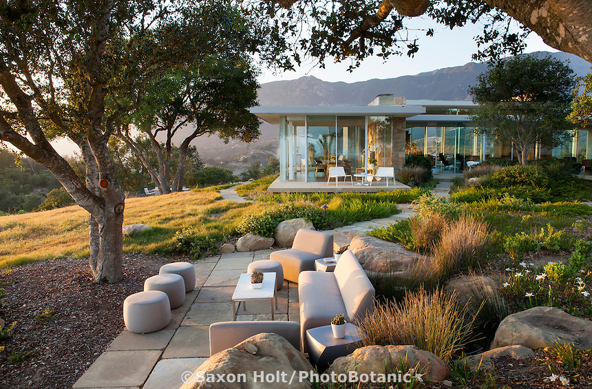 Outdoor stone patio sitting area under Oaks next to modern glass hilltop home with California native plant garden, Santa Barbara,
