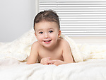 Cute smiling two year old baby boy lying on a bed under a blanket after taking a bath
