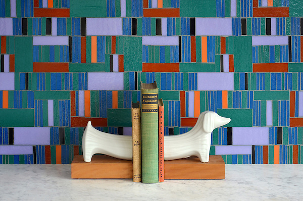 Kente, a hand-cut glass mosaic shown in Athos, Juhl, Blair, Rhode, Rolly and Obsidian, is part of the Erin Adams Collection for New Ravenna Mosaics.<br /> <br /> Dachshund bookends are from Jonathan Adler.<br /> Take the next step: prices, samples and design help, http://www.newravenna.com/showrooms/