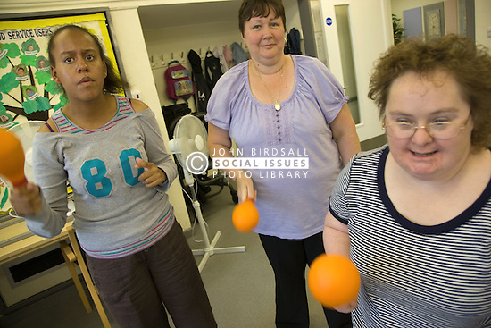 Group of Day Service users with learning disabilities and Care Assistant playing maracas,
