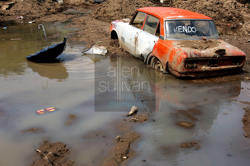 A once-for-sale car sits stuck in mud. In early October a nearby river sent torrents of water and mud through the town, near prosperous Antigua, and destroyed several homes after rains associated with Hurricane Stan inundated parts of Central America. Torrential rains and mudslides killed or made missing thousands of Guatemalans in early October.<br />