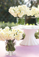 A cake stand has been used in this inventive flower arrangement with masses of creamy narcissi in simple glass vases