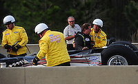 Mar. 9, 2012; Gainesville, FL, USA; NHRA pro mod driver Mike Janis (second from right) is helped from his car by members of the safety safari after crashing during qualifying for the Gatornationals at Auto Plus Raceway at Gainesville. Janis would be unhurt in the incident. Mandatory Credit: Mark J. Rebilas-