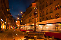 A tram passes by the Musketeer Fountain (Schutzenbrunnen) on Marktgasse with the Prison Tower (Kafigturm) in background, Bern, Canton Bern, Switzerland