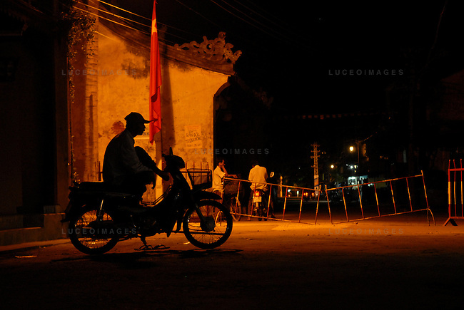 "A motor bike driver called a ""xe om"" waits for a customer in Hoi An, Vietnam."