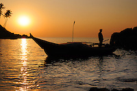 Silhouette of fisherman with nets in the sea on his boat at the dusk. Palm trees on the hill on background
