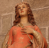 Statue of St Philomena, virgin martyr, wearing a crown of roses and holding an arrow and a palm of martyrdom, 18th century, in the Saint-Hilaire-D'Aude Abbey, built 11th - 14th centuries and closed 1748, when it became a parish church, Saint-Hilaire, Aude, Languedoc-Roussillon, France. St Hilary built the first chapel on this site in the 6th century. In the 10th century his relics were discovered here and the church, then an abbey, rededicated to him. Picture by Manuel Cohen