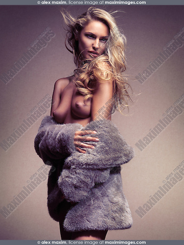 Beautiful half nude topless woman with flying long blond hair wearing a fur coat over nude body