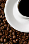 Stock photo of a Cup of black coffee on a saucer standing on coffee beans background Artistic stil life