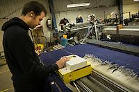Operaio con tappi acustici all'interno di un fabbrica di tessuti gestisce una macchina a controllo numerico Bute tartan mills
